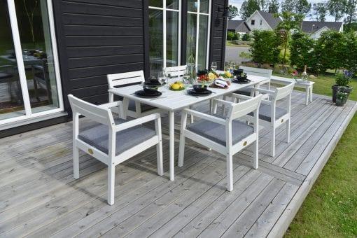 Stoltö matbord och stolar vita på uteplats.